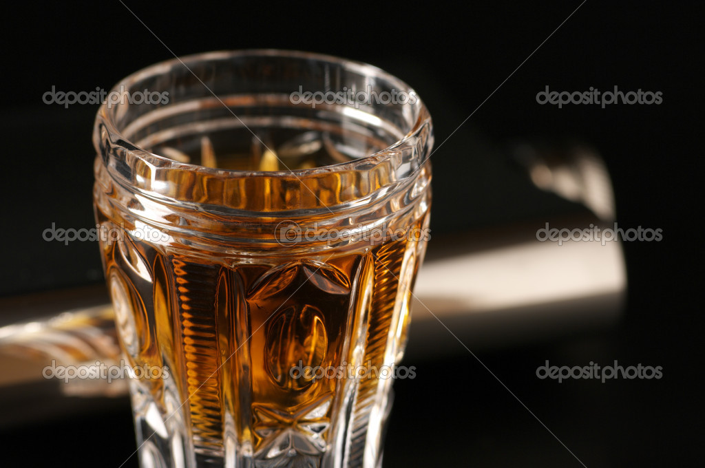 Faceted glass of cognac and stainless flask on black background.  Stock Photo #2915283