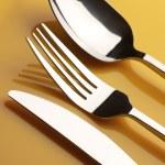 Silverware on yellow — Stock Photo