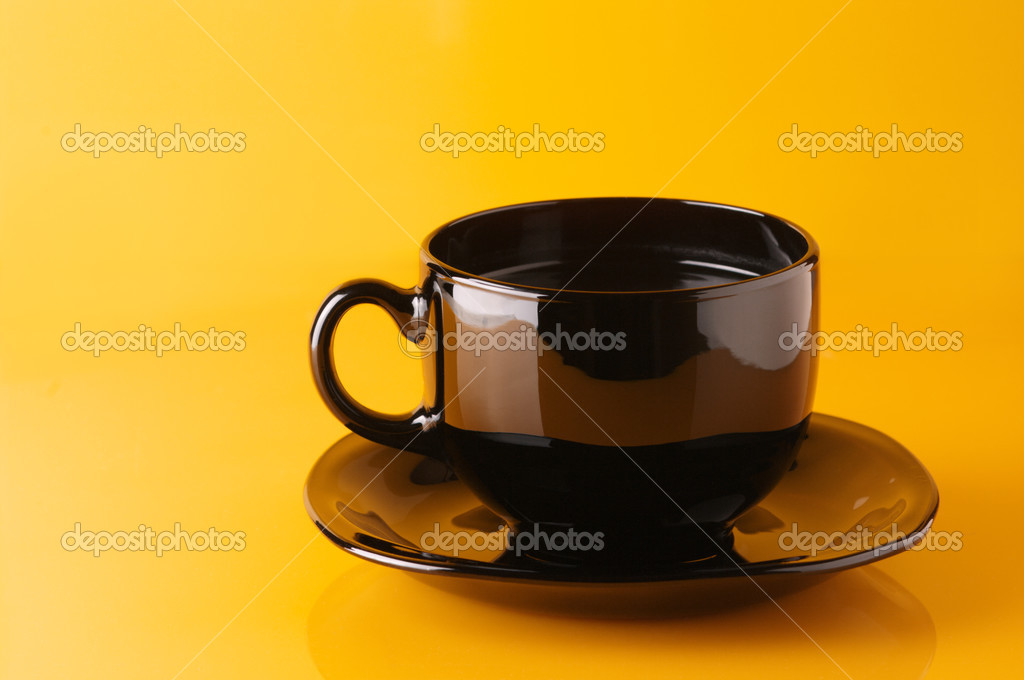 Black glass cup of coffee with saucer on yellow background. — Stock Photo #2947689