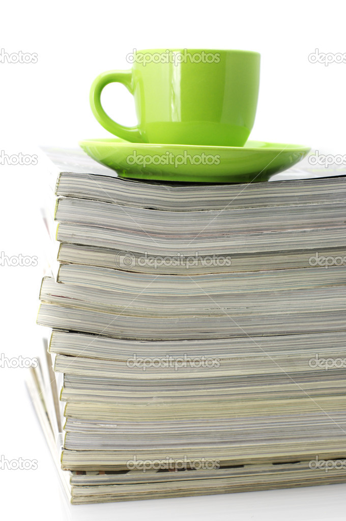 Stack of magazines and green cup of coffee isolated on white background. — Stock Photo #2950451