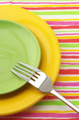 Multicolored plates and fork — Stock Photo