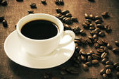 Vintage cup of coffee and beans — Stock Photo