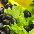 Black olives, greens and oil - Stock Photo