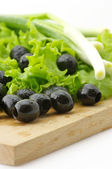 Black olives and greens — Stock Photo