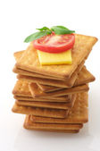 Crackers with cheese, tomato and basil — Stock Photo