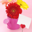 Colorful gerberas in watering can and note holder - Stock Photo