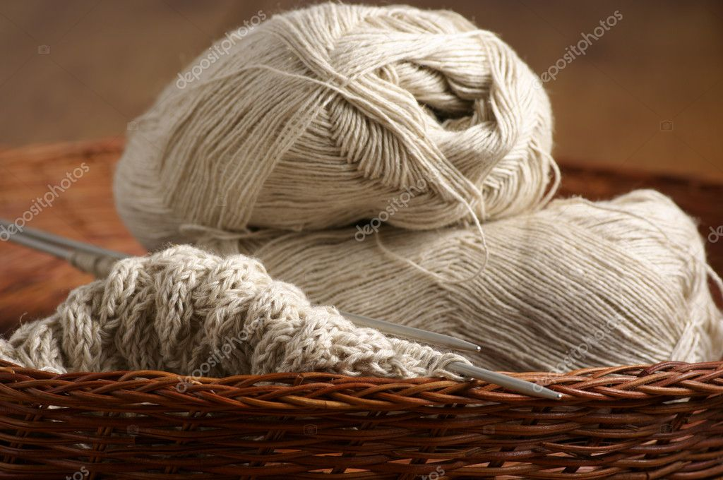 Linen yarn and knitted fabric with needles in wicker basket. — Stock Photo #3781020
