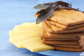 Crackers, cheese and basil — Stock Photo