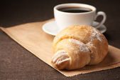 Croissant and black coffee — Stock Photo