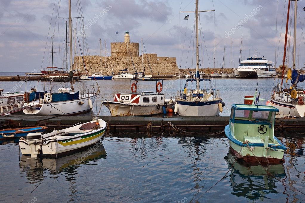 Yachts and boats in Mandraki harbor against lighthouse, Rhodes, Greece — Stock Photo #2721972