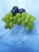 Grapes and plums in a glass — Stock Photo