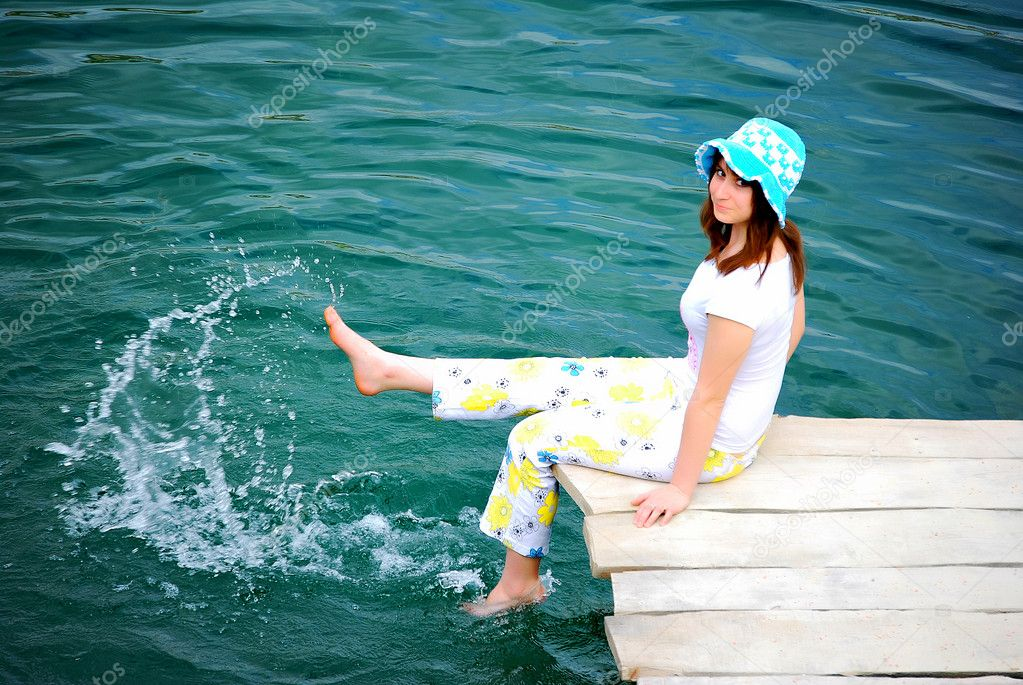 Young girl dabble in water by lake — Stock Photo #3455746