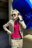 Blonde speaks by payphone — Stock Photo