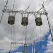 Постер, плакат: Electric transformers against clouds