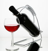 Red wine bottle in holder — Stock Photo