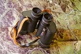 Binoculars on map — Stock fotografie