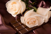 White roses on brown silk and chocolate — Stock Photo