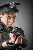 Beautiful policewoman aiming a gun — Стоковое фото