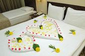 Bed suite versierd met bloemen en handdoeken. — Stockfoto