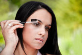 Beautiful women combing eye brows — Stock Photo