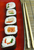 Sushi futomaki with chopsticks — Stock Photo
