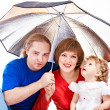 Happy family under umbrella — Stock Photo