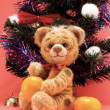 Toy tiger with oranges under a fur-tree — Stock Photo