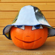 Pumpkin with female face in a children's hat — Stock Photo