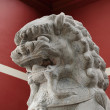 Stone lion statue before the red wall - Stock Photo
