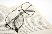 Opened book and glasses — Stock Photo