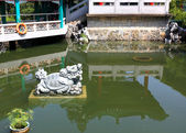 Lion statue in chinese garden pool — Stock Photo