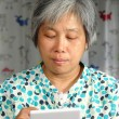 Middleage chinese woman playing handheld game console — Stock Photo