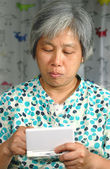 Chinese woman playing handheld game console — Stock Photo