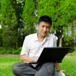 Stock Photo: Asian man using computer outdoor
