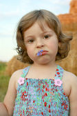 The sad girl with a cornflower in lips — Stock Photo