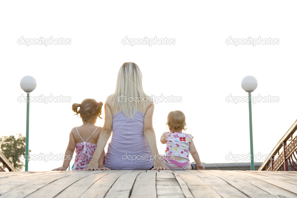 Mum to daughters sit next in the summer evening and admire a decline — Photo #3730065