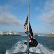 Royalty-Free Stock Photo: USA Flag waves on the back of a ferry as it sails out of Oakland