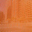 Orange sheet with open dots letting in bits of the city — Stock Photo