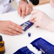 Stock Photo: Young doctor check blood-sugar level