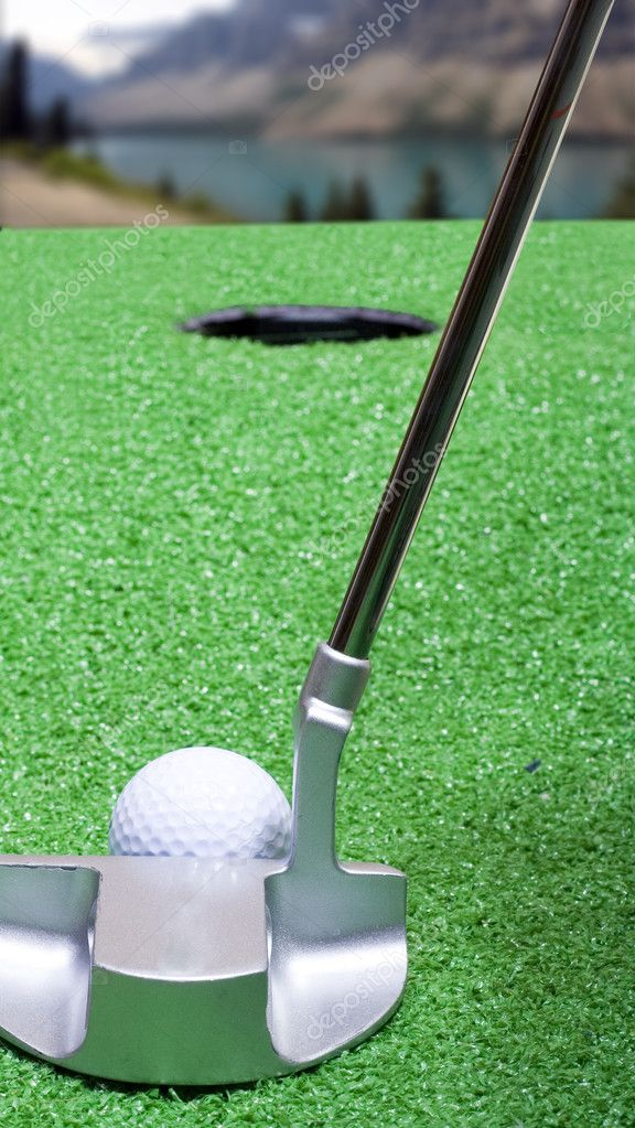 A putter lines up a golf ball on a mountainside green.  Stock Photo #2744062