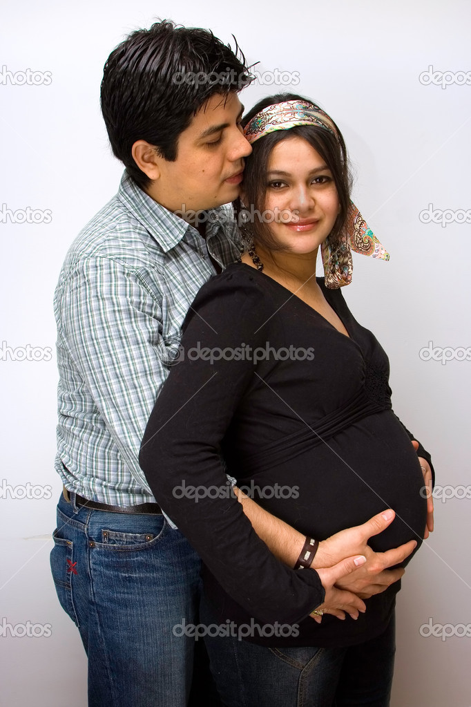 Parents expecting a baby. Father holds the belly of the mother and mother placed her hands on top of fathers hands.  Stock Photo #2738908