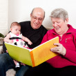 Stock Photo: Grandparents reading book to baby girl.