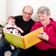 Grandparents reading book to baby girl. — Stock Photo