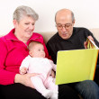 Family reading book to baby — Stockfoto