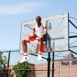 Royalty-Free Stock Photo: Basketball player sitting in hoop