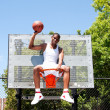 Champion basketball player sits in hoop — Stock Photo