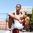 Basketball player sitting on ball — Stock Photo