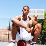 Basketball player sitting on ball — Stock Photo