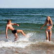 Couple playing in ocean water — Stock Photo