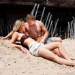 Couple laying in sand — Stock Photo